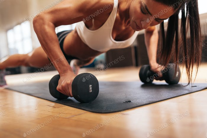Muscular woman doing push-ups on dumbbells