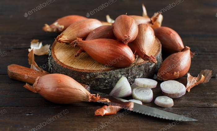 Organic small onions on wooden table