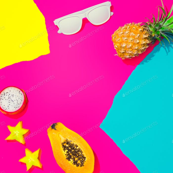 Creative tropical layout with tropical fruit. leaves and colorful vivid papers. Abstract colors