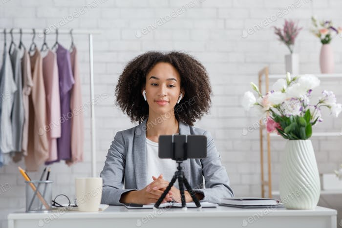 Online fashion blogger advice. Serious african american woman looking at webcam