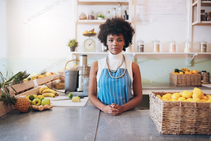 Young african woman behind juice bar counter