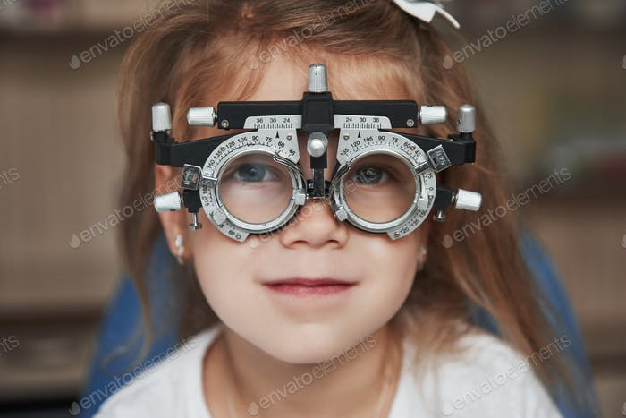 Focused portrait of little girl in phoropter looking straight into the camera