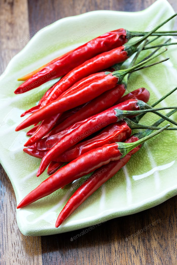 Red chili peppers on plate on wooden background