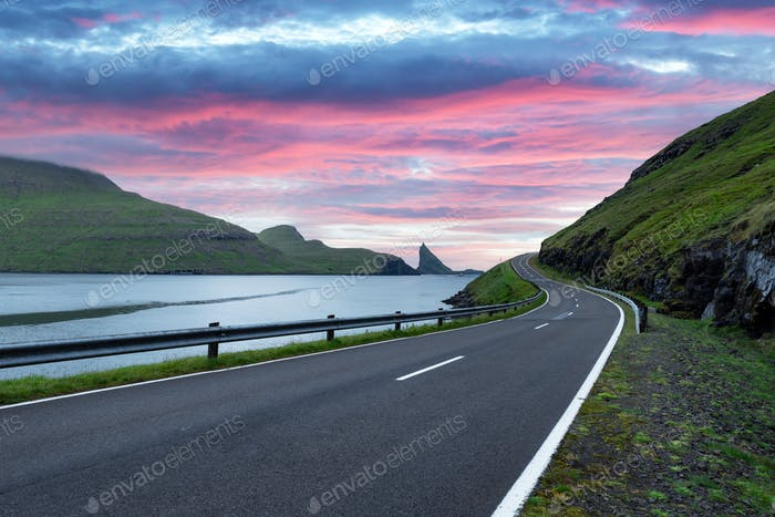 Dramatic evening view of road and Tindholmur cliffs