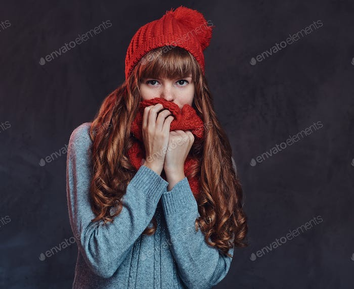 Redhead girl wearing a warm sweater and scarf