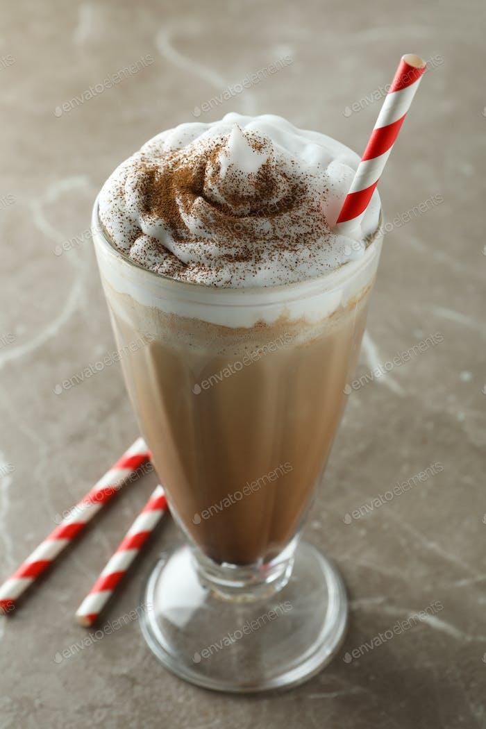 Glass of chocolate milkshake and straws on gray table