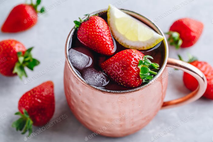 Refreshing iced Moscow mule alcoholic cocktail in copper mugs with strawberry and lemon
