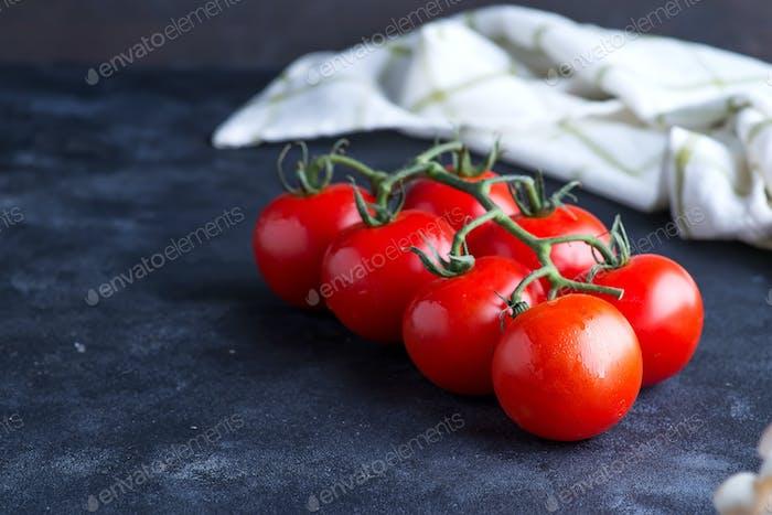 Frische Kirschtomaten als Kochzutaten für Salat oder Gericht auf dunklem Hintergrund