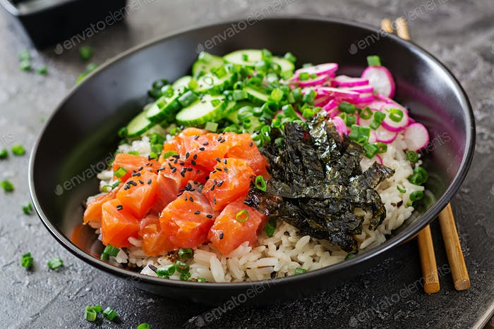 Hawaiian salmon fish poke bowl with rice, radish,cucumber, tomato, sesame seeds and seaweeds.
