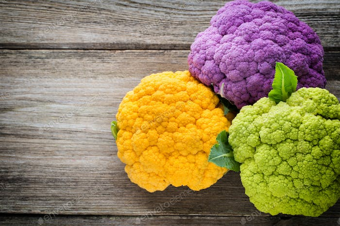 Rainbow of eco cauliflower on the wooden table.