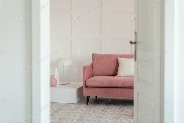 Open door to modern white living room interior with pastel pink sofa, coffee table and lamp