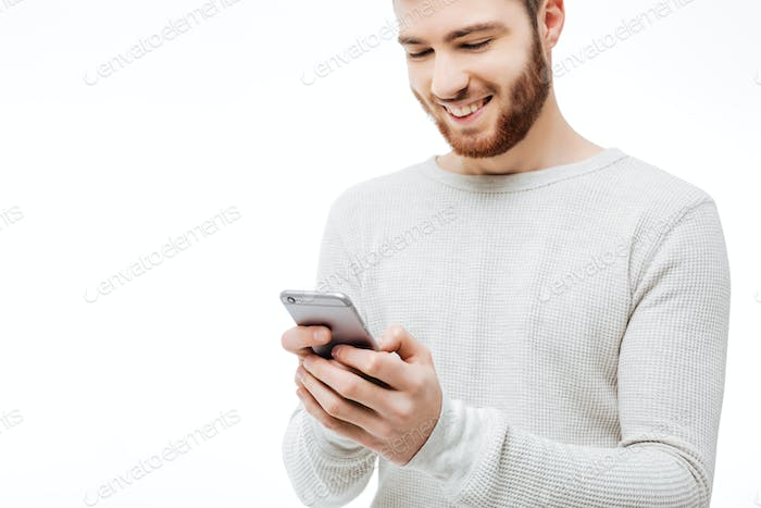 Happy bearded guy typing message on the smartphone isolated