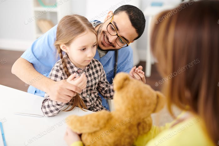 Playful  Pediatrician Working with Little Girl