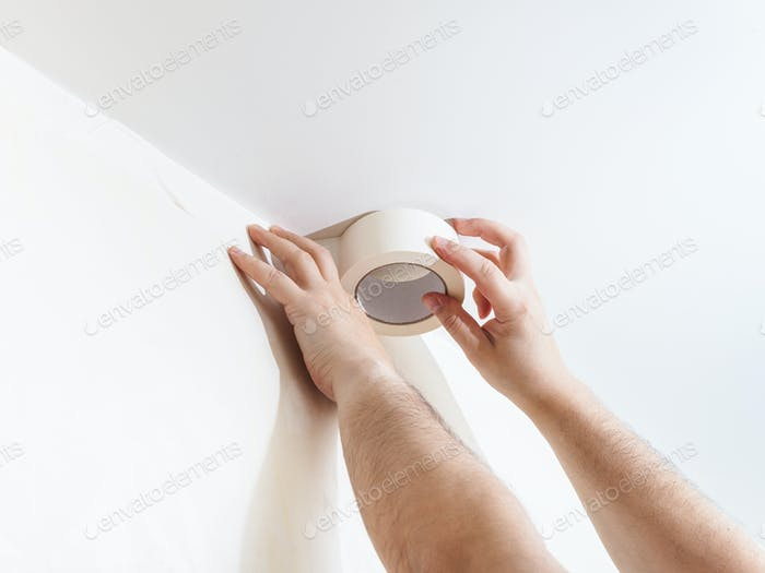 Worker mounts sticky tape on wall before painting