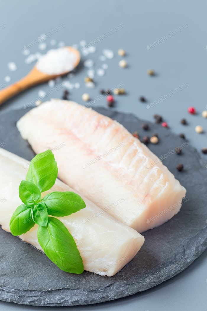 Fresh raw cod fillet with spices, pepper, salt, basil on stone p