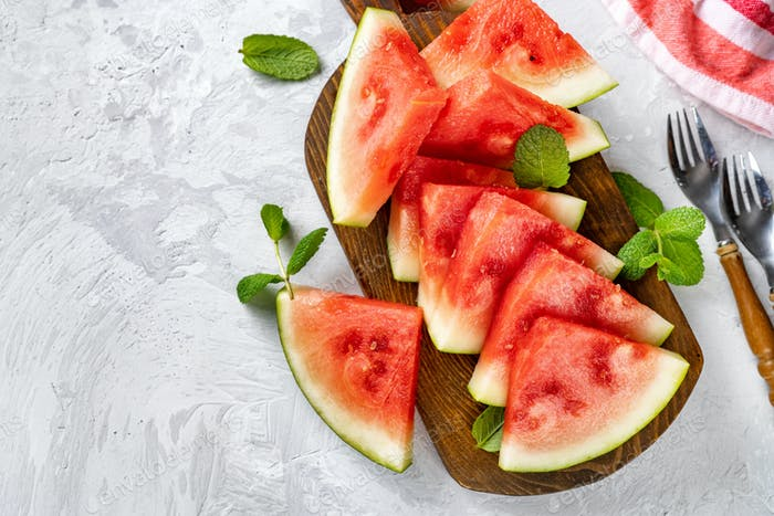 Close up of sweet and juicy watermelon slices on wooden board and light background