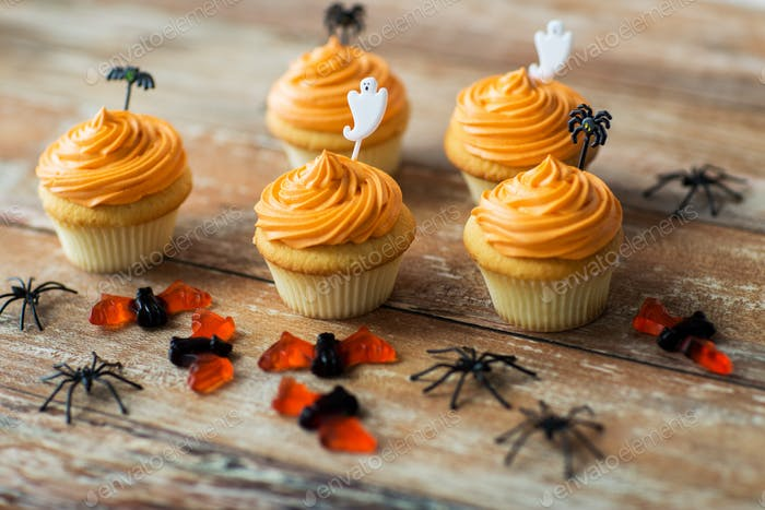 halloween party decorated cupcakes on wooden table