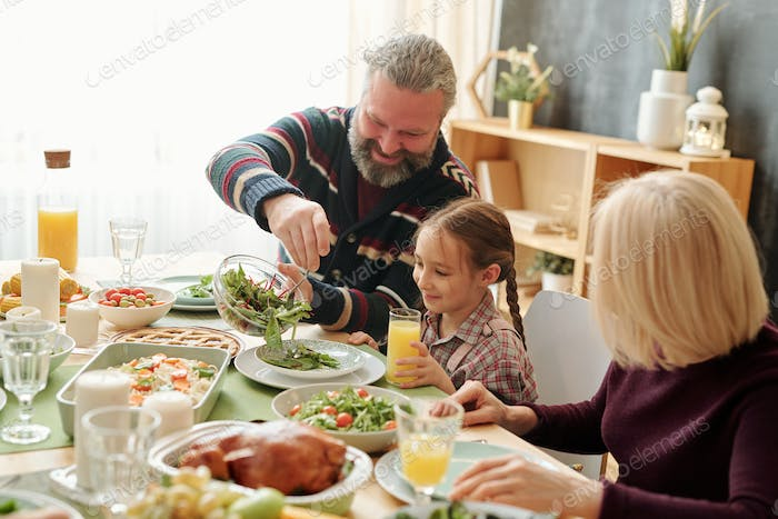 Happy grandpa giving salad to his cute granddaughter by festive table