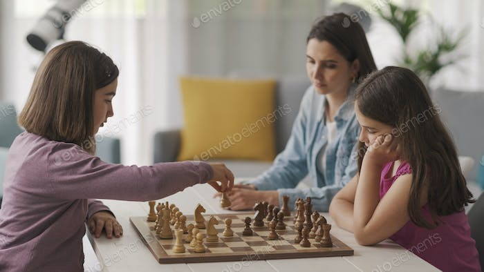 Girls playing chess together at home