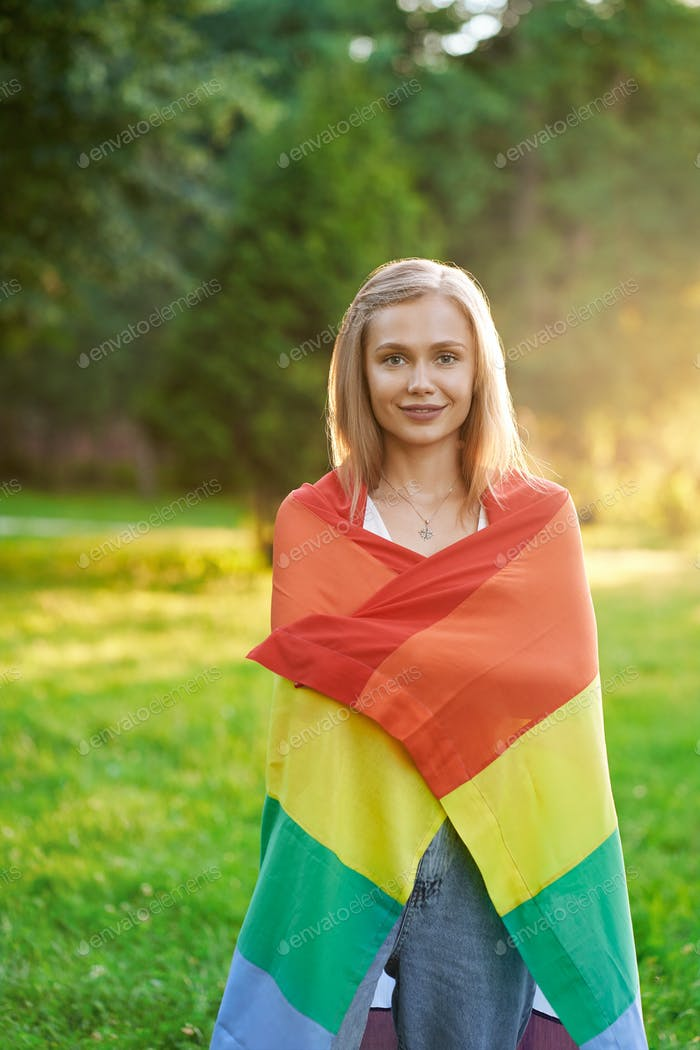 Smiling tolerant woman holding lgbt flag outdoors