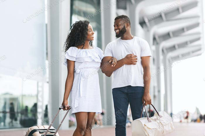 Happy african newlyweds walking at airport building with luggage