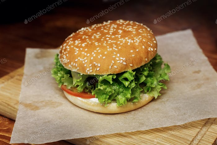 Serving cheeseburger or hamburger with salad and tomatoes on wooden desk