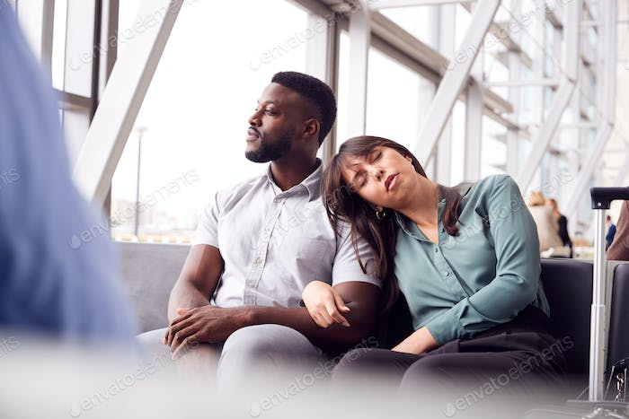 Tired Business Couple Sitting By Window Waiting In Airport Departure Lounge