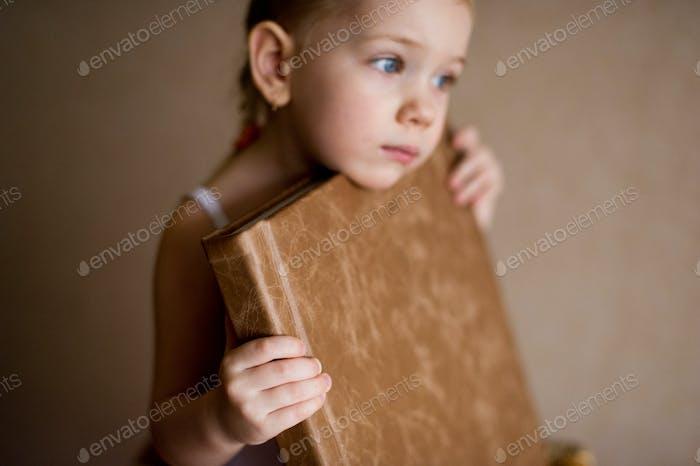 ein kleines Mädchen hält ein Fotobuch aus naturbraunem Leder