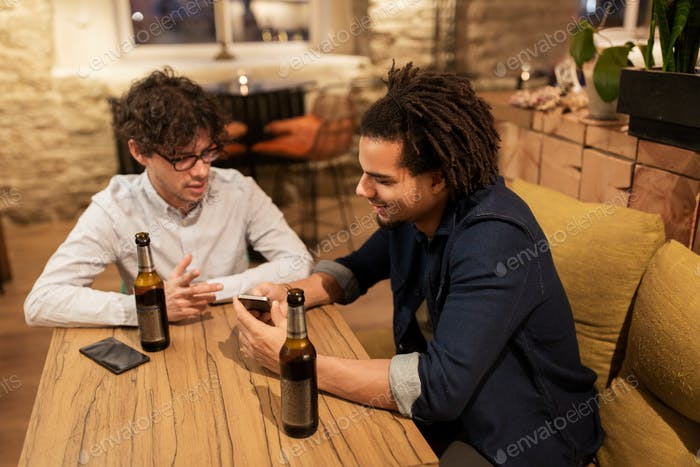 men with smartphones drinking beer at bar or pub