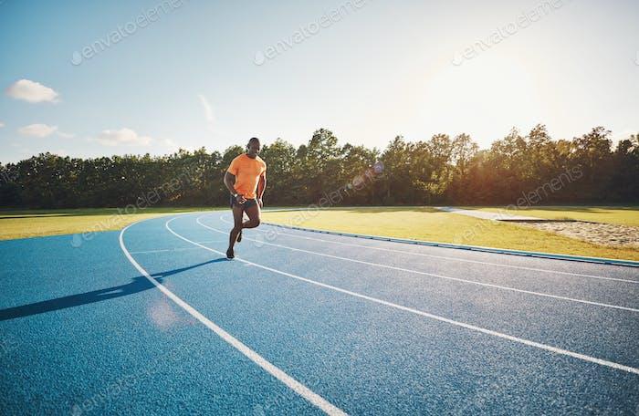 Сосредоточив молодой спортсмен, бегущий в одиночку на гоночной трассе