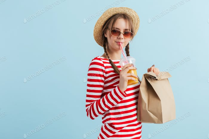 Young beautiful smiling girl with two braids in straw hat and red sunglasses drinking orange juice