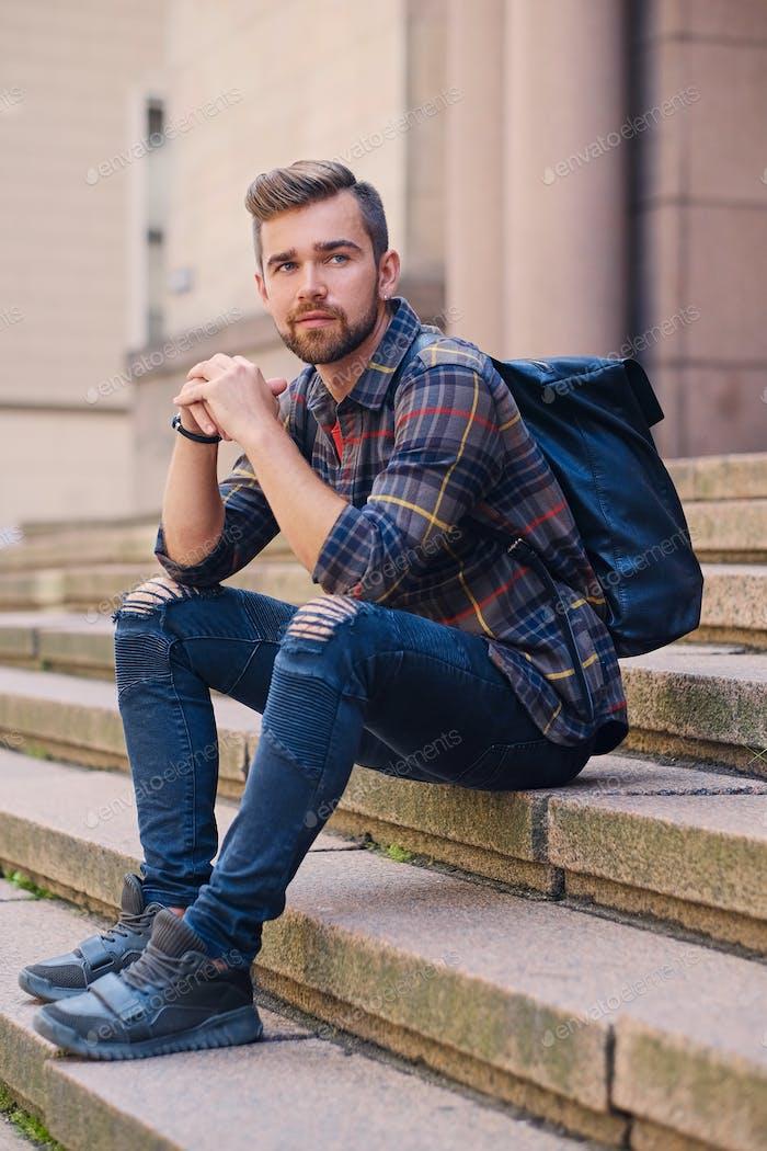A man sits on a step.