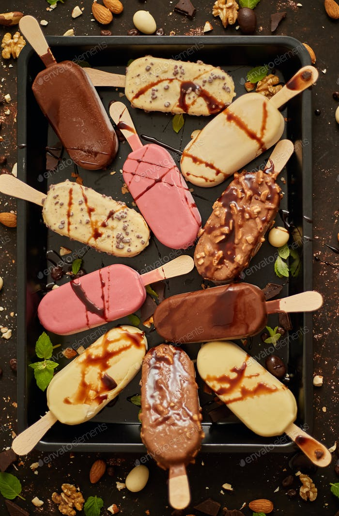 Assortment of various popsicle ice cream, white and dark chocolate, with almonds, rusty background