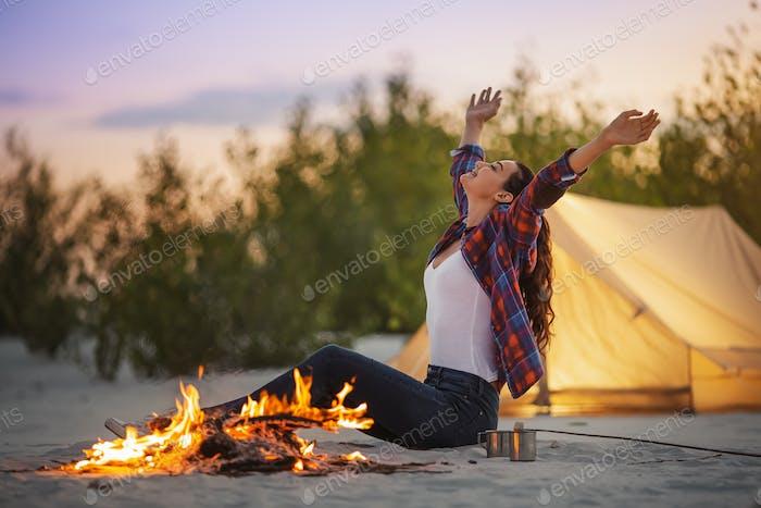 Tourist Frau im Camp in der Nähe Lagerfeuer