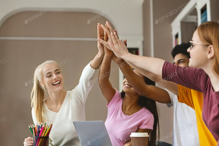 Enthusiastic students raising hands up together in library