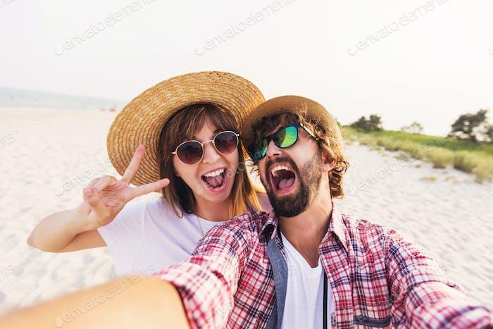Happy traveling couple in love taking a selfie