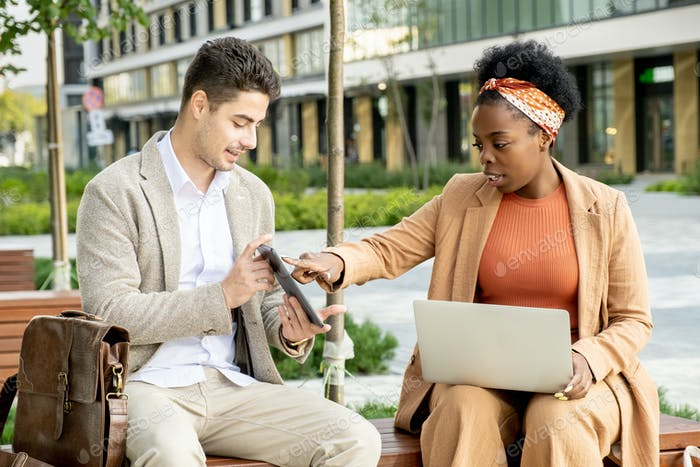 Young confident businesswoman of African ethnicity pointing at screen of tablet
