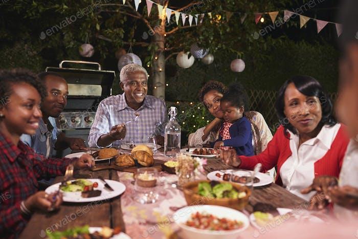 Multi generation family eating dinner in garden, close up