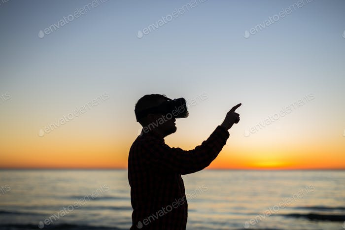 Future has come. Man wearing virtual reality goggles