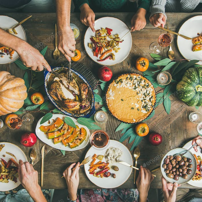 Friends feasting at Thanksgiving Day table with turkey, square crop