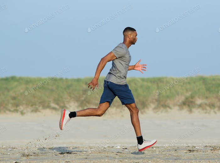 African american man jogging at the beach