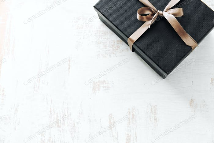 Gift wrapped in dark paper on white background