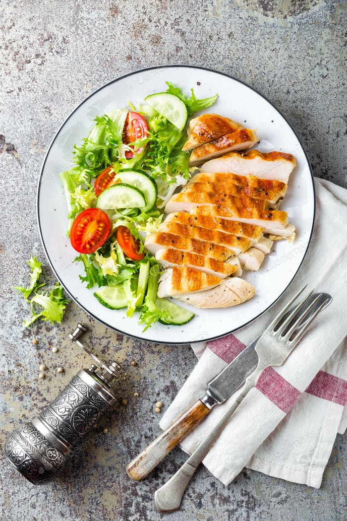 Chicken breast or fillet, poultry meat grilled and fresh vegetable salad of tomato