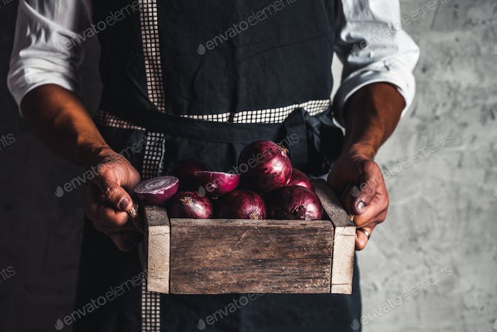Fresh red onion in hands an old box. On wooden background