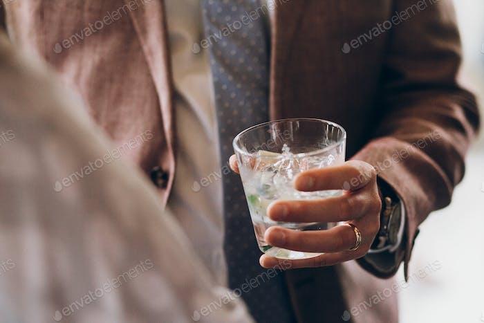 Hände von stilvollen Menschen jubeln mit Gläsern Whisky