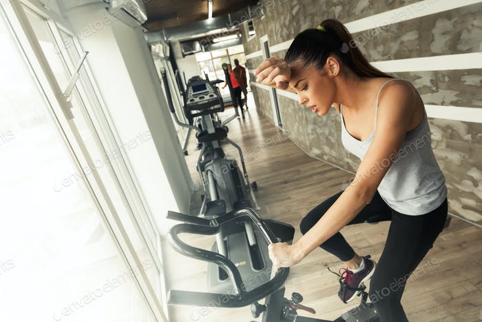 Tired woman doing cardio in gym