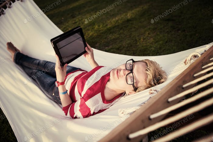 woman using a tablet computer while relaxing on hammock