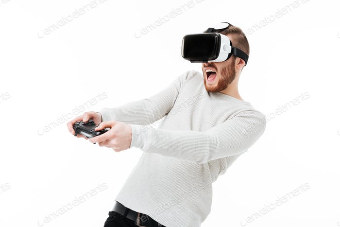 Young emotional man using virtual reality glasses and playing video game over white background