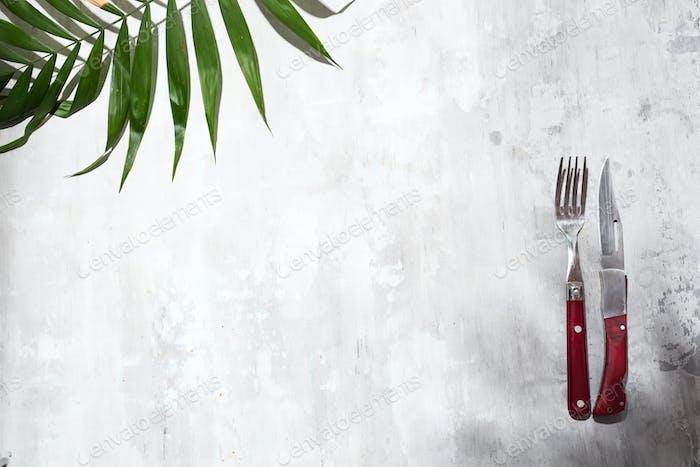 Messer und Gabel für Essen und Palme verlassen auf dem steingrauen Hintergrund, Draufsicht.