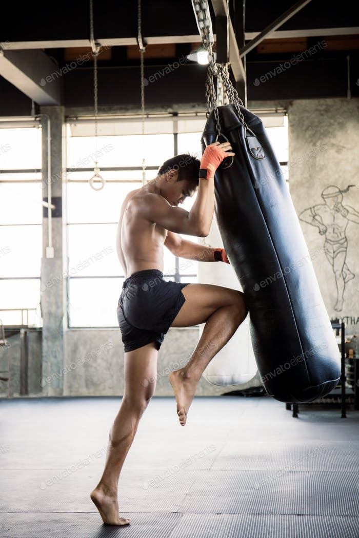 Boxers are training their knees with punching bag